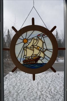 Stained glass tall ship with hand lathed ships wheel frame.