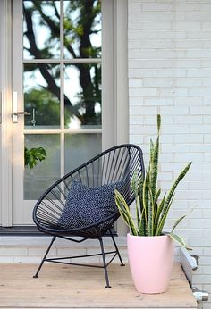In this understated back porch setting, the Acapulco chair flies under the radar as this pretty pastel planter takes the stage.