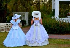 Inspecting the immaculate grounds before the ball, these sisters of the South prepare to host the arriving carriages to their palatial plantation home.