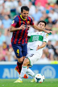 Cesc Fabregas of FC Barcelona is brought down by Alberto Rivera of Elche FC during the La Liga match between Elche FC and FC Barcelona at Estadio Manuel Martinez Valero on May 11, 2014 in Elche, Spain.