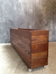 Reclaimed hardwood planter. Stained dark with steel castors. Contact us today for custom timber planter boxes.