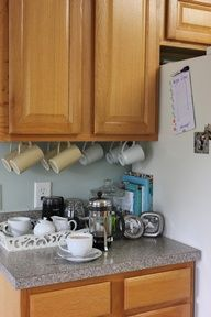 Hang coffee cups under kitchen cabinet with hooks...makes for extra space!