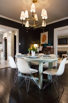 love the moody wall color, brass chandelier and the modern, plastic chairs.