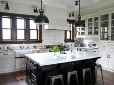 A traditional kitchen done with white subway tile to the ceiling features a kitchen island, schoolhouse lighting, marble counter tops and a farmhouse sink as seen on HGTV.com.