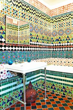 Vibrant multicolored and patterned floor to ceiling tiled bathroom.
