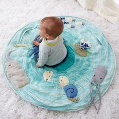 Marine themed baby activity mat lets your baby explore the wonders of the seven seas from the comfort of the nursery.  It features a school of appliqued and embroidered sea creatures, rouched fabric for a wavelike texture and soft padding for extra comfiness.  Baby-sized snorkel and fins are not needed.