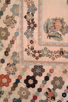pieced and applique bedcover with central square section with applique printed cotton motifs of pair of pheasants under fruiting tree amidst flowers; with applique flower/oak leaf motifs to each corner of this central square; followed by band of meandering stars, pieced; followed by large section of all-over pattern of alternating rows (right across quilt, except central panel) of stars (seven hexagons) and hexagons of coloured fabrics on a background of cream pieced hexagons; Outer ban...