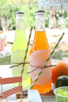 Citrus drinks in a bottle with paper straws and doilies