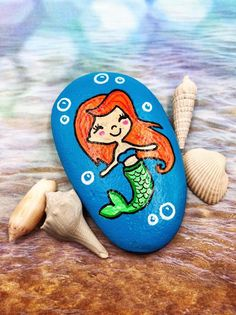 This hand painted mermaid rock makes a great birthday party favor! Click through… This hand painted mermaid rock makes a Pebble Painting, Pebble Art, Stone Painting, Rock Painting Ideas Easy, Rock Painting Designs, Stone Crafts, Rock Crafts, Mermaid Party Favors, Mermaid Parties