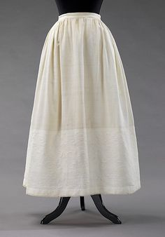 Petticoat, 1865-69. American, cotton. MMA. 2009.300.3234. [Unusual style; looks like the lower part is woven as matelasse. Flat front does indicate an elliptical hoop shape. Hem is trimmed with what may be densely crocheted lace.]