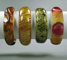 Group of Four Bakelite Bracelets  Each translucent, two reverse carved, another with confetti inclusions, the other with spherical decoration. Widest 1 1/8 inches.    Sold for 1,900 (Includes Buyer's Premium)
