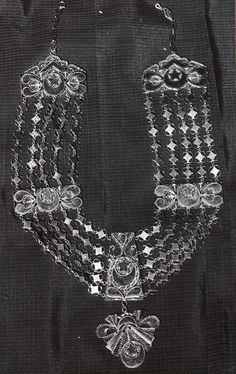 Comoros - Grande Comore, Moroni | Black and white photo of a 'hara' necklace.  These gold necklaces are offered to the wife at the 'big wedding'; Comorian men take many wives but only celebrate one 'big wedding' with great pomp