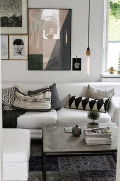 Layered textiles and pillows with a white, pink and gray color scheme living room.