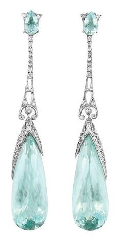 A Pair of Edwardian Platinum, Aquamarine and Diamond Pendant-Earrings, circa 1910. Each surmounted by a pear-shaped aquamarine, joined by a pierced platinum diamond-set filigree link, suspending a drop-shaped aquamarine, approximately 38.00 carats. #Edwardian #earrings