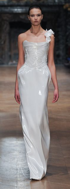 """Tony Ward - white, floor-length dress in a material that gives the appearance of supple patent leather. I think there are """"hidden"""" pockets at the hips and I wish there weren't, as it causes the material to """"bulge there, and what girl wants that?"""