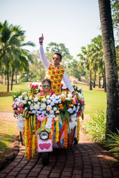 Fun groom entry with the bride riding a floral auto rickshaw
