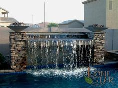 Swimming pool water feature with stacked stone columns and fire pots. - www.lonestaraz.com