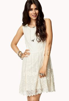 A sleeveless dress featuring a floral embroidered mesh overlay. Round neckline. Buttoned keyhole ...