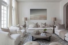 Chic living room boasts a gray abstract art piece standing over an ivory slipcovered sofa adorned with gray metallic pillows flanked by round French end tables and gray double gourd lamps.