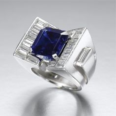 SAPPHIRE AND DIAMOND RING Of architectonic design centring on a square step-cut sapphire weighing 6.43 carats, the wide tapered mount set with baguette diamonds