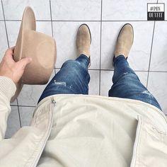 botas chelsea, calça jeans, blusa longline off-white, jaqueta off-white e chapéu bege.