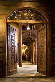 This Larry Andren-designed North American hunting lodge in Bend, Oregon, features carved doors and custom ironwork of my own design. We showed the bone structure of the columns as a colonnade. Lodge Look, Windows And Doors, Front Doors, Entry Doors With Glass, Fireplace Seating, Santa Fe Style, Front Door Design, Main Door, Columns