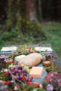 A table spread with natural decor - purple grapes, red berries and flowers.