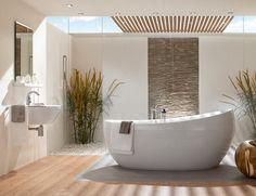Badkamer met ovaal vrijstaand bad. De parel van deze badkamer is ongetwijfeld het fraaie vrijstaande bad. Dit ovale ligbad is gemaakt van de kunststof Quaryl en voelt daarom lekker warm aan en is makkelijk schoon te houden. De kleuren mooi in balans en zorgt voor een rustgevend sfeer. Interessant is ook de afwisseling van ruwe en gladde materialen zoals de kiezels op de vloer gecombineerd met het parket.