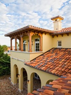 This Spanish style home features clay tiles for the roofing and a white/cream exterior. The bottom and top floors both show an arcade of arches. The roof that covers the top porch area is flat, which you see a lot in Spanish style roofs.