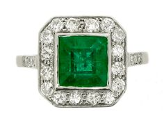 Emerald and diamond cluster ring, circa 1950. A platinum ring set with one central square step cut emerald in a rubover collet setting with an approximate weight of 2.00 carats, encircled by a single row of sixteen round old cut diamonds in bead settings with an approximate total weight of 0.80 carats, above an ornate openwork gallery, flanked by raised shoulders supported by cheniers and set with six round eight cut diamonds in bead settings with an approximate total weight of 0.06 carats…