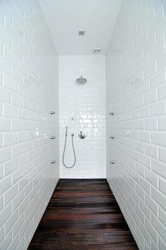 Badet er utradisjonelt innredet med tregulv, til og med i dusjen. Veggene er dekket av hvite subway-fliser.