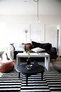 O marrom, pontuado no pufe, almofada e ramos de trigo, ao fundo, aquece esta sala de tapete listrado e mesa de centro em cimento.