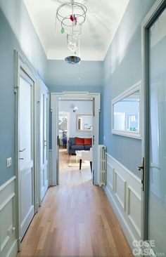 Una casa di 50 mq con tante soluzioni da copiare: porte in legno recuperate, boiserie in gesso a parete, ripostiglio mimetizzato e altro ancora.