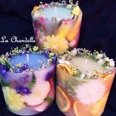 Put candle in a smaller container and add flowers to the sides and add more wax