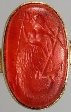 Gemme: Fischschwänziger Seedämon. Römisch, Mittlere Kaiserzeit 2. Jh. n. Chr. Karneol, kräftig orangefaren, schwach durchscheinend. Triton mit struppigem Haar, nacktem menschlichen Oberkörper und in der Taille beginnendem dicht geschupptem Fischschwanz. Er hält in der Rechten einen Dreizack, in der Linken einen Anker mit Tau.