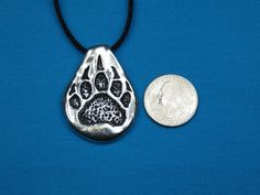 Welcome!  This listing is for one solid silver pewter bear paw necklace done in the Neo Primitive style. It was completely hand sculpted and handmade by my husband. Hanging from a cord, It measures approx: 1 1/4 wide x 1 3/4 tall, or 3.3 cm wide x 4.4 cm tall. This is not a thin, hollow casting, this piece is solid and has quite a good heft to it! :)  **All pendants come with a standard 32 inch (81.28cm) hand knotted Black Satin necklace cord that can be adjusted to size by the wea...