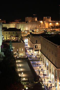 Jerusalén, Israel: El contraste de las luces brillantes de la zona de negocios con la vieja pared en el fondo.