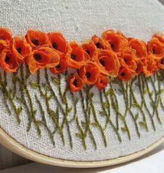 embroidery (flowers made with synthetic fabric rounds with heated/melted edges then pinned in center with thread, nice textural effect)