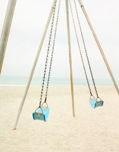 Turquoise swings on the beach.