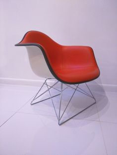 Herman Miller Eames Fiberglass armchair with orange vinyl upholstery and a cats cradle wire base