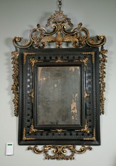 An Early 18th Century Venetian Ebonised & Parcel Gilt Mirror.