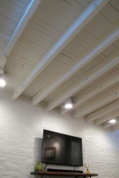 Exposed ceiling in a shallow basement - paint the rafters instead of covering them up to make the space look larger