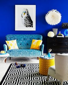 The soft turquoise pattern of the love seat, and the yellow accents, make the saturated blue walls more approachable.