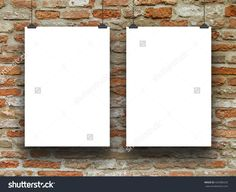 Close-up of two blank frames hanged by clips against red brick wall background