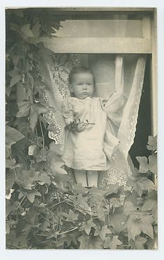 Post mortem photo of child standing in window - notice someone behind the curtain holding the child.