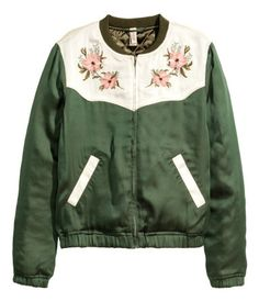 Green. Lightly padded satin bomber jacket with embroidered yoke, zip at front, and contrasting side pockets. Ribbed trim at neckline and elastication at