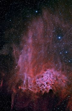 IC 405 is named the Flaming Star Nebula,The material that appears as smoke is mostly interstellar hydrogen, but does contain smoke-like dark filaments of carbon-rich dust grains. The bright star AE Aurigae, visible near the nebula center, is so hot it is blue, emitting light so energetic it knocks electrons away from surrounding gas. When a proton recaptures an electron, red light is frequently emitted, as seen in the surrounding emission nebula.
