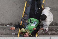 美聯社攝影師Narciso Contreras作品  當地時間2012年10月24日,敘利亞阿勒頗,政府軍的炮彈襲擊當地一家面包店,造成多名平民傷亡,一名男子試圖將受傷的女子轉移到醫院治療。