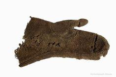 """""""Vöttur eða vettlingur, saumaður úr mórauðu vaðmáli. Fannst í jörðu í Görðum á Akranesi, talinn frá 9. eða 10. öld."""" [Mitten or glove, sewn from homespun vaðmál. Found in the ground at a farm in Akranes, considered to be from the 9th or 10th century.] Þjóðminjasafn Íslands, acc. no. A-1940/B-1881-76."""