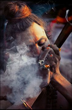 Sadhu smoking a mixture of tobacco and hashish, or charas, in a straight clay pipe called a chilum
